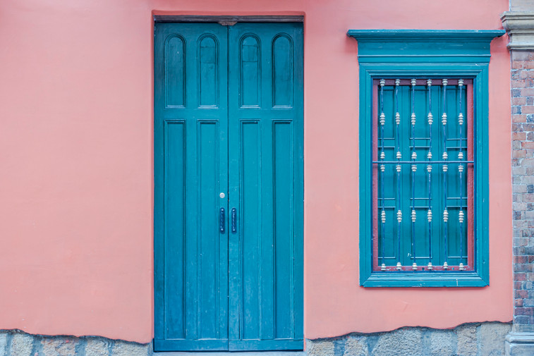 Blue door and window in a pink wall