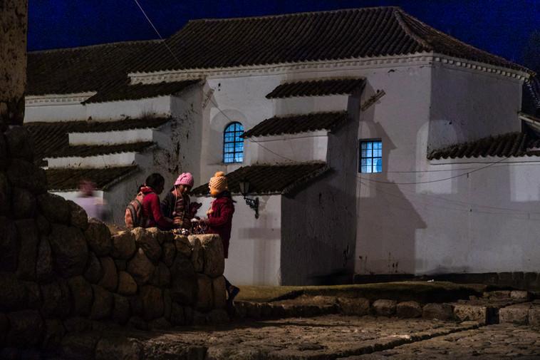 Young girls chatting at night in Chincheros, Peru