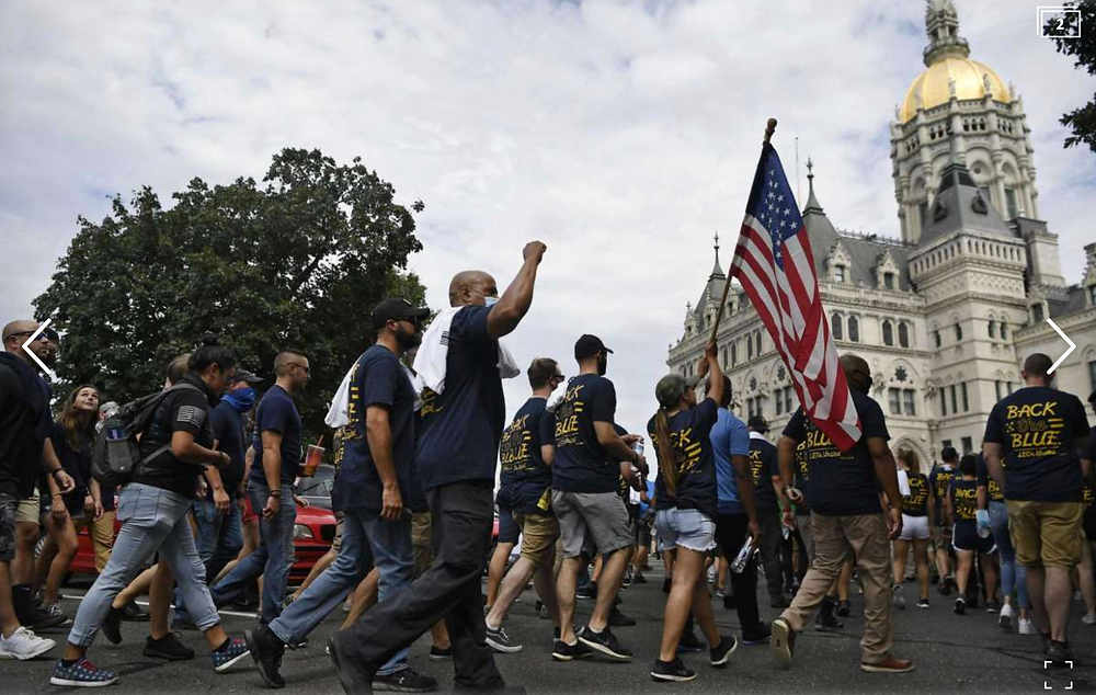 People participating in a rally to show support for law enforcement officers march toward the state Capitol July 23, 2020, in Hartford.