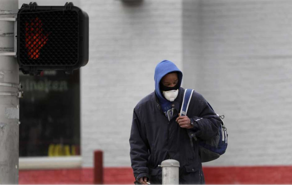 A man wears a protective mask as he waits to cross a street.
