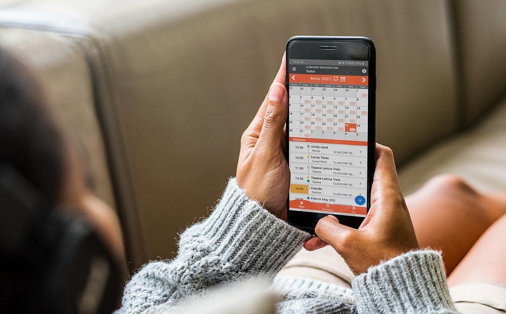 sistema para clínica de estética, mullher fazendo agendamento de consulta online pelo celular