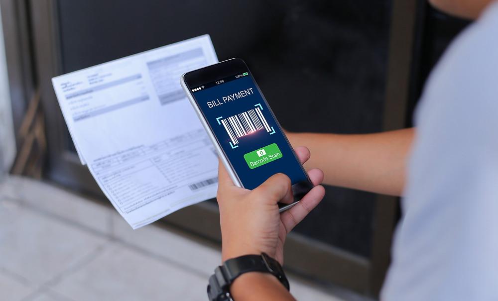 meios de pagamento para dentistas, homem pagando boleto com o celular