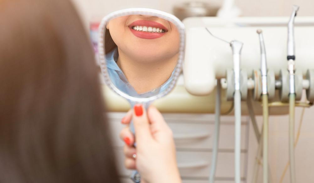 experiência do paciente na odontologia, paciente segurando o espelho e sorrindo no consultório do dentista
