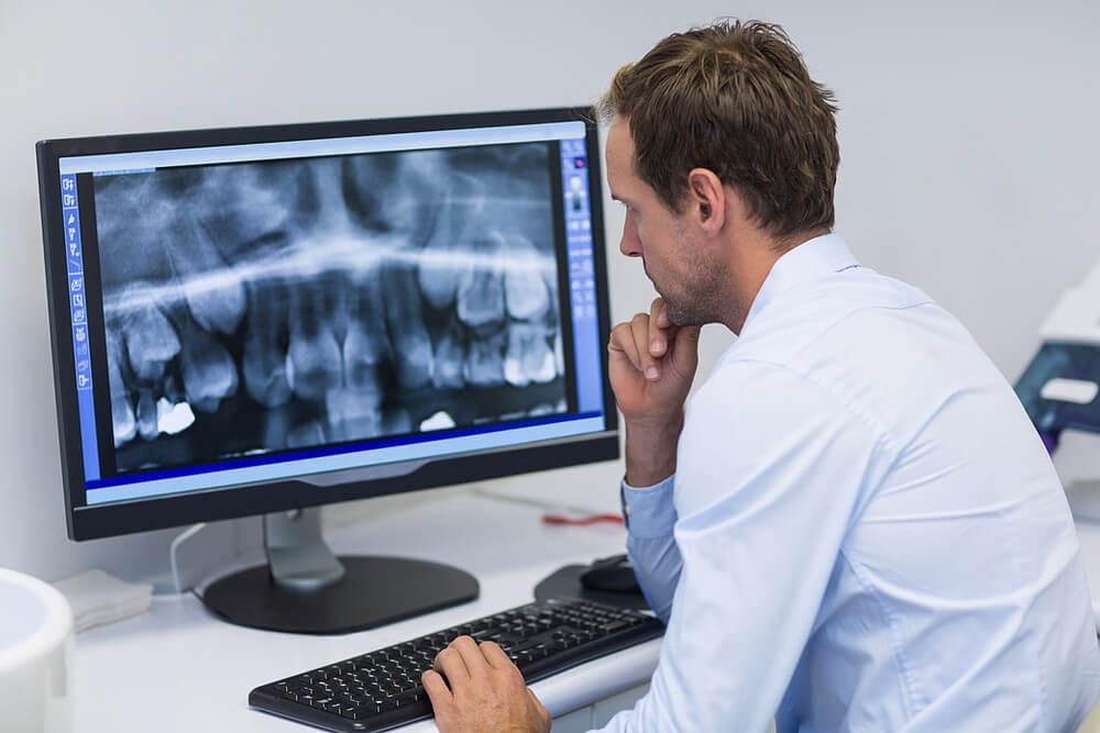 dentista sentado em frente ao computador olhando uma radiografia digital