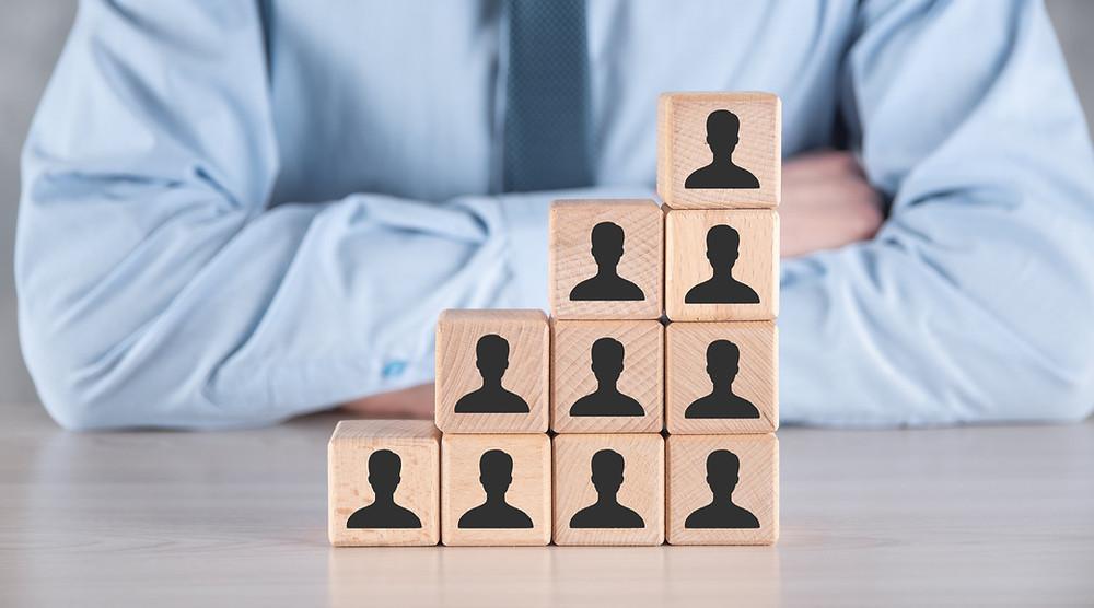 dicas de estética, gestor olhando uma pilha de bloquinhos representando a sua base de clientes.