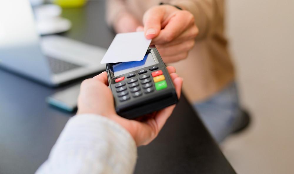 meios de pagamentos para dentistas, paciente realizando pagamento na maquininha de cartão
