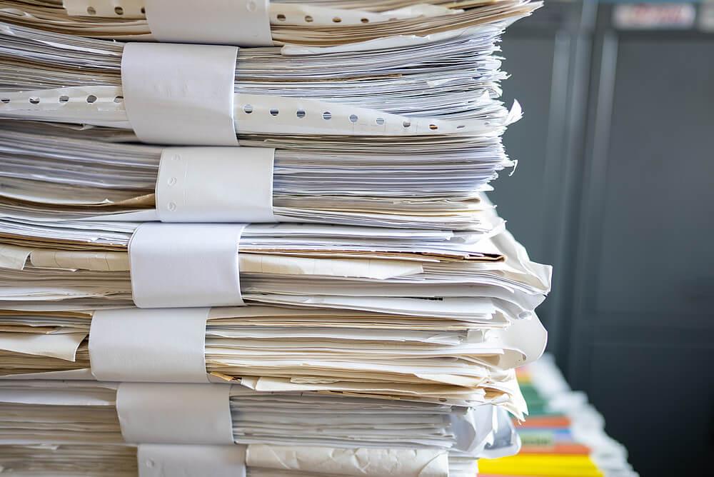 pilha de arquivos de papel em cima de uma mesa