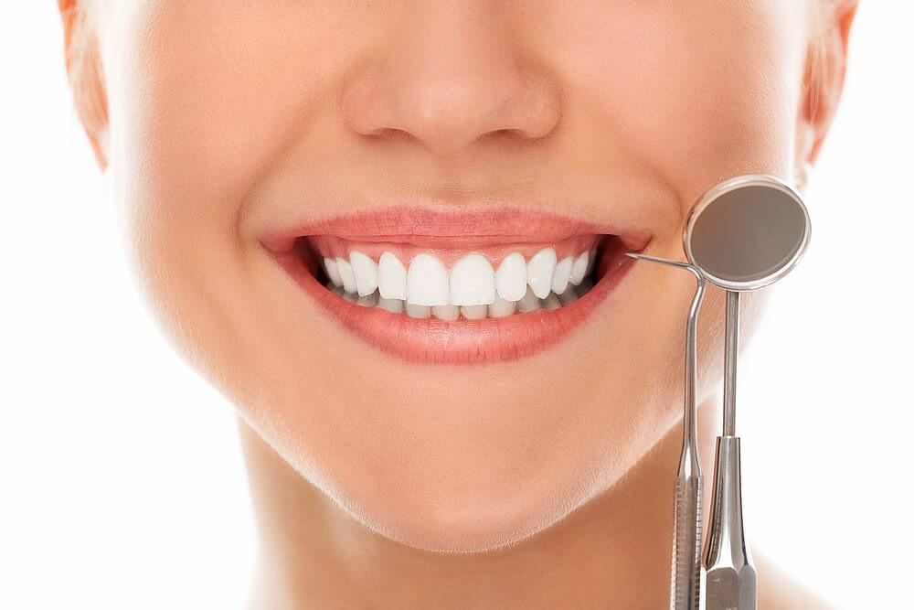 foto de um sorriso bonito com acessórios de uso do dentista
