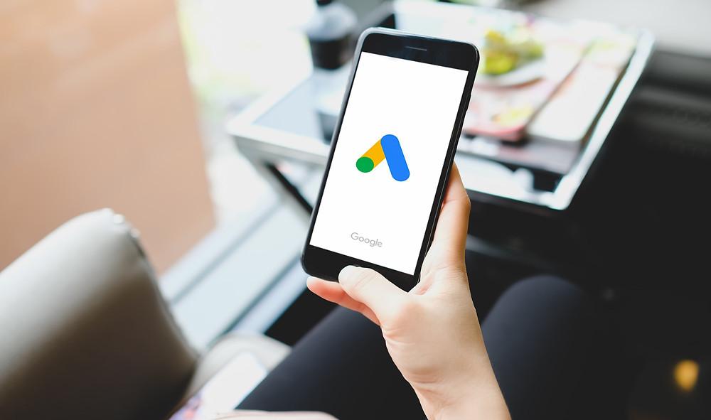 captação de pacientes, mulher jovem olhando anúncios do google no celular