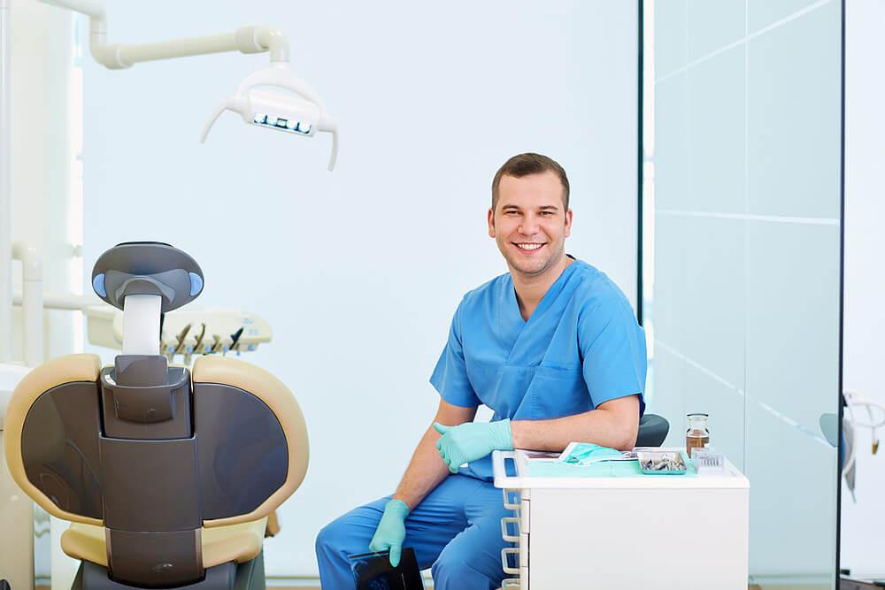 marketing odontológico, dentista sentado sorrindo em seu consultório