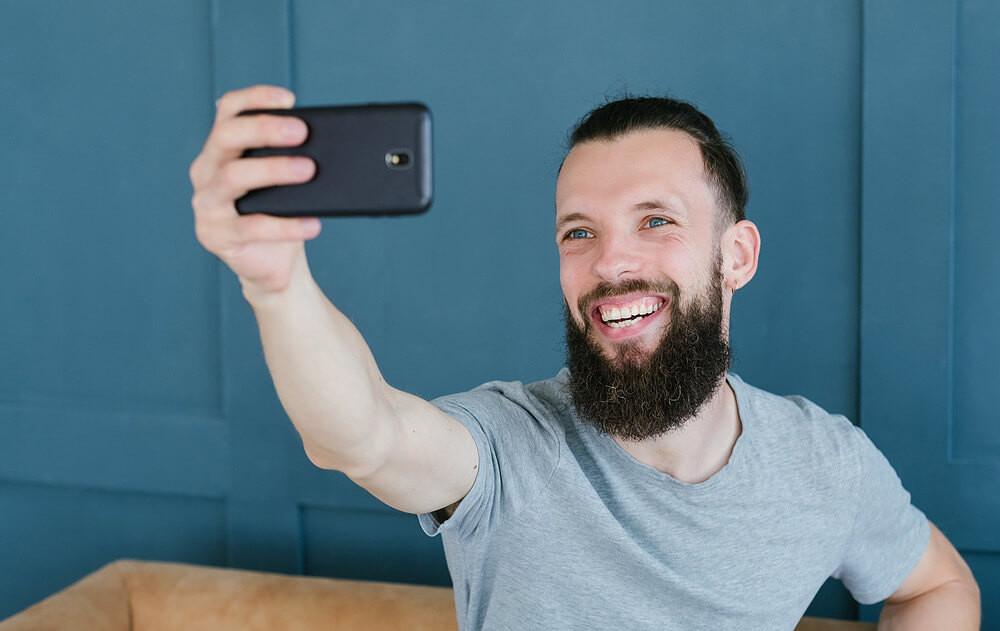 captação de pacientes na odontologia, homem fazendo foto com o sorriso