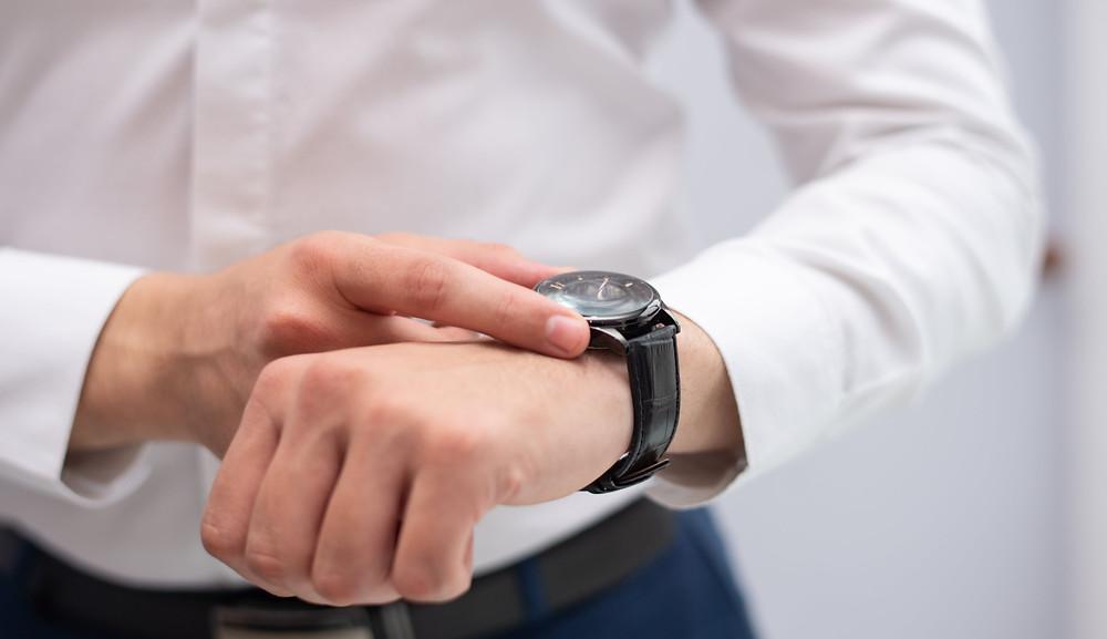 experiência do paciente na odontologia, homem olhando as horas em um relógio de pulso