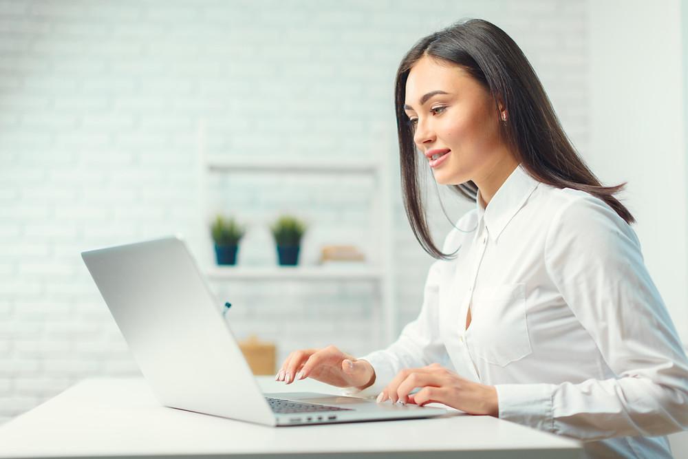 Gestão de clínica jovem verificando no computador informações da sua clínica de estética