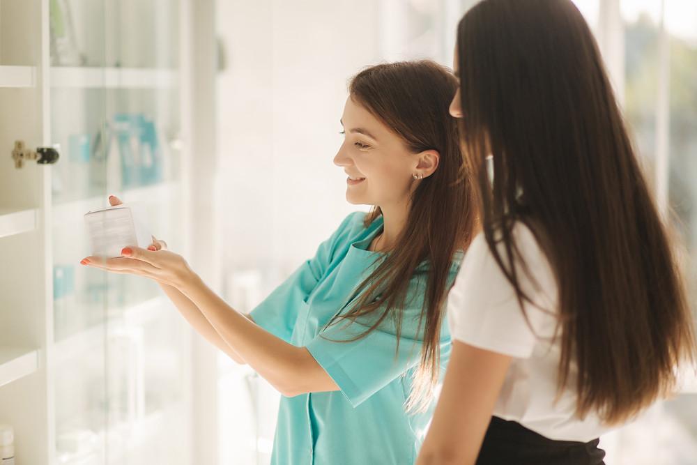 estética, profissional apresentando um cosmético para a cliente