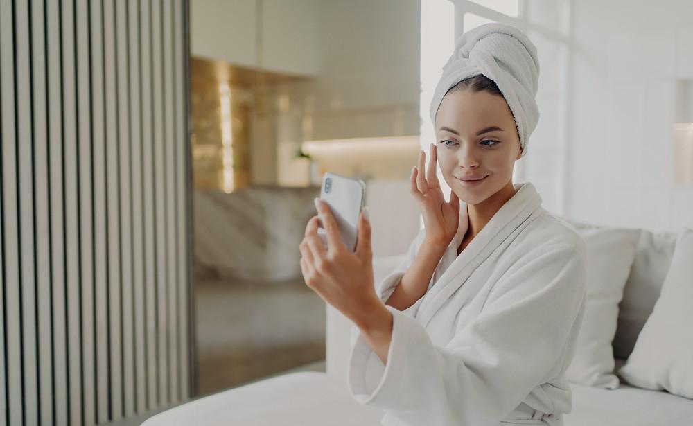 como montar uma clínica de estética, mulher se observando no celular