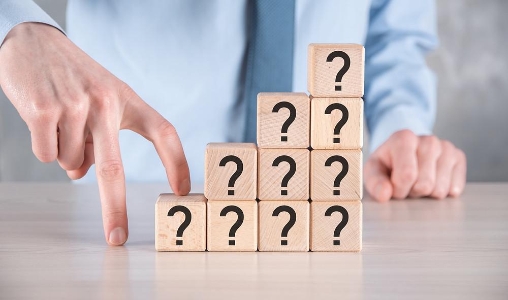 como montar uma clínica de estética, Empresário segurar e colocar a forma de bloco de cubo de madeira com pontos de interrogação na mesa cinza