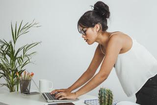 אישה כותבת בלפטופ