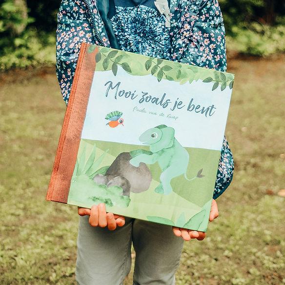 Kind houdt prentenboek Mooi zoals je bent vast