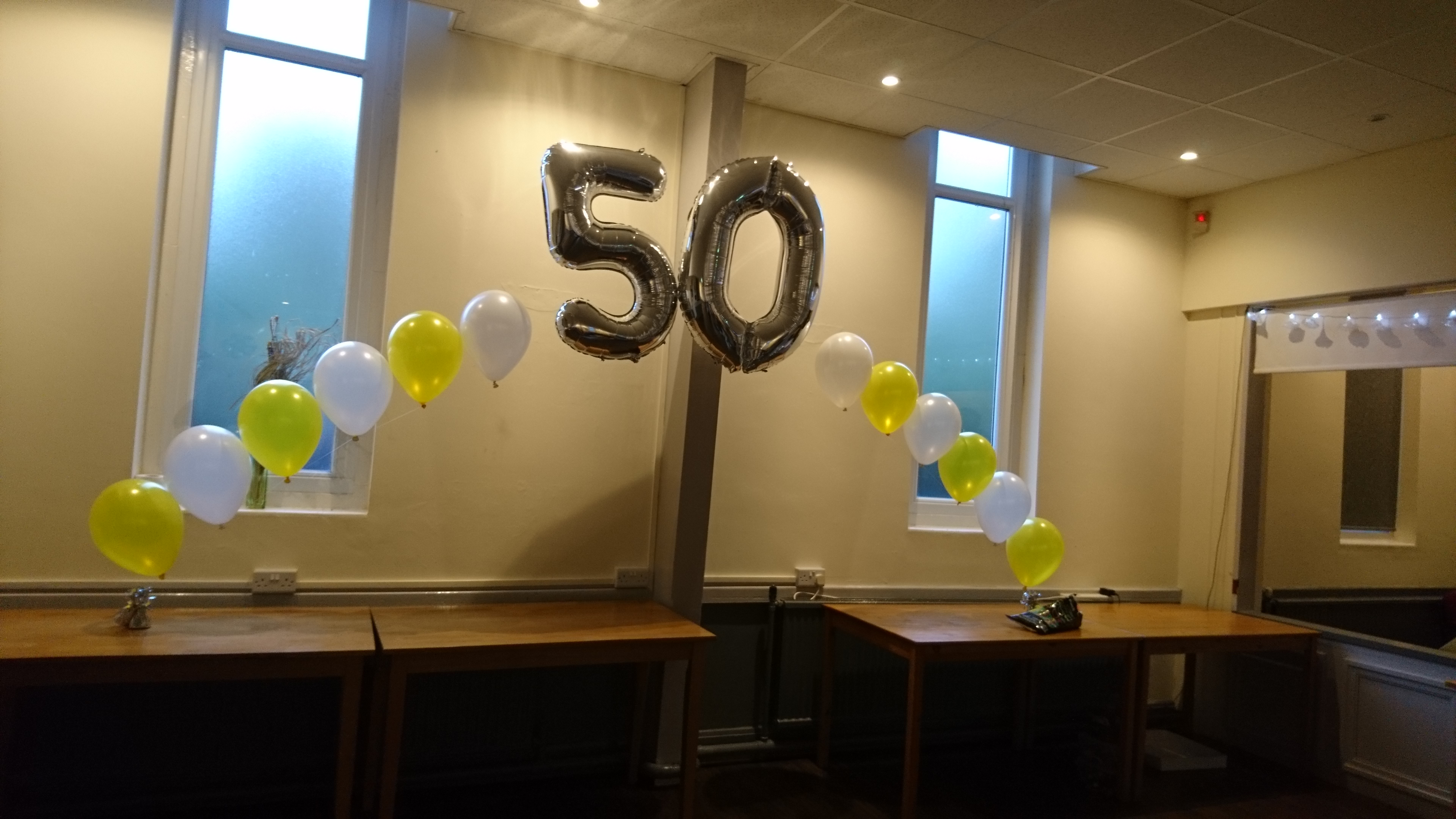 yellow and white number balloon arch den