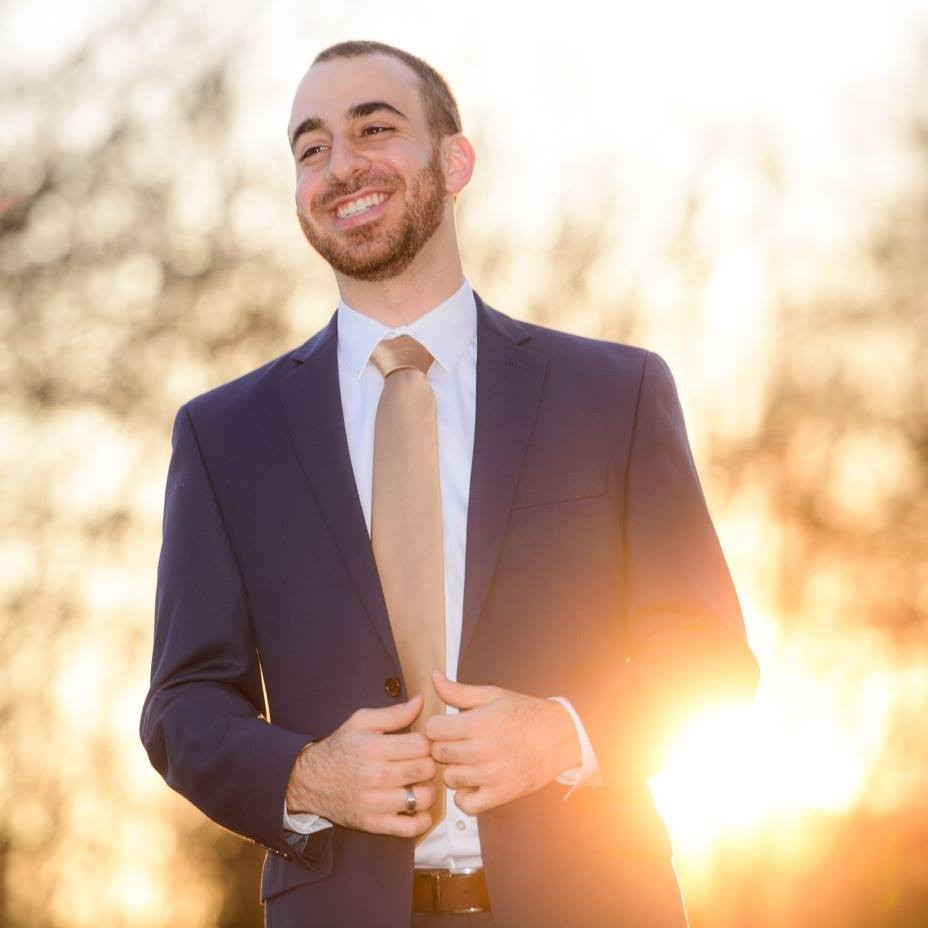Omar in a suit with the sunset behind