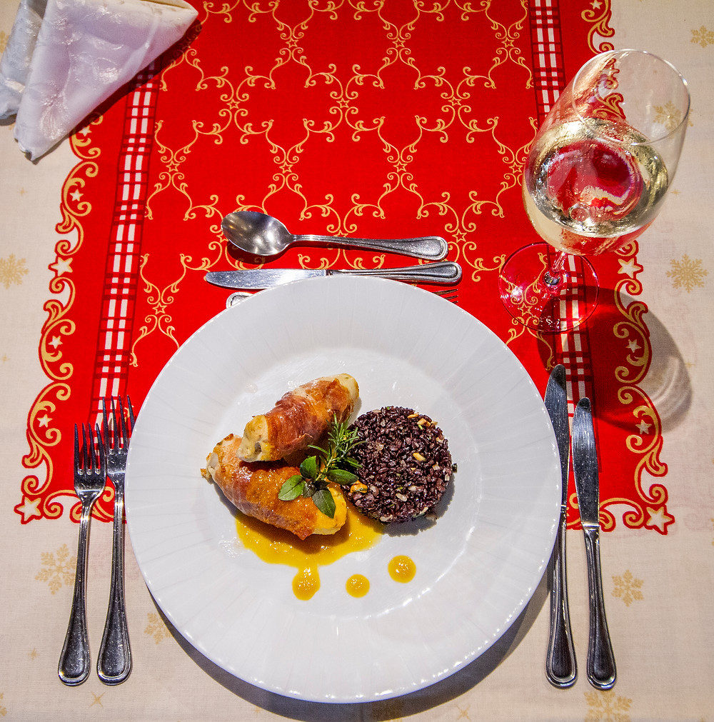 Peito de peru recheado com damasco e queijo de cabra envolto em jamon serrano ao molho de laranja servido com arroz negro e castanhas