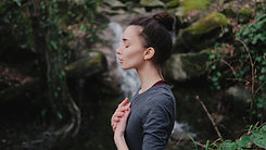 Young woman practicing breathing yoga pranayama outdoors in moss forest on background of waterfall.