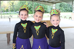 3 young Flying Irish dancers, standing with arms around each other & smiling, wearing team costumes of embroidered leotards & crowns