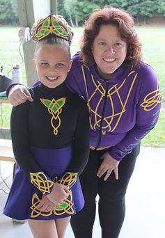 Flying Irish teacher in team jacket posing with young dancer in team costume with celitc designs