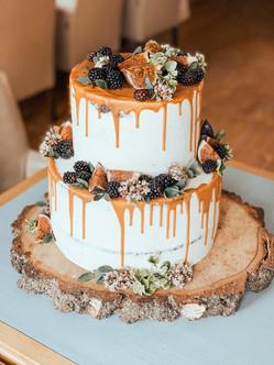 Svatební dort s polevou a ovocem - fíky, ostružinami a živými květy