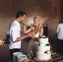 Krájení svatebního dortu s živými květy a ovocem ženichem a nevěstou