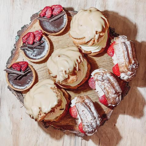Větrníky s karamelovou polevou, eclaires s jahodami a čokoládové tartaletky s malinami