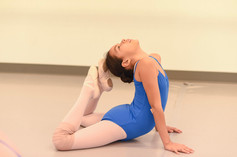Young ISB ballet student posing on the floor stretched to touch the back of her heat with her toes at the studio in Eastlake, CA.