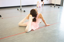 Young ISB Twirl ballet dancer posing with her toes touching her head at studio in Chula Vista, CA. Dancer is located 6 feet away from other dancers and wearing a face mask.