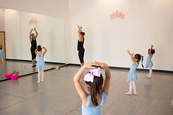 Twirl Aqua ISB ballet dancers following Ms. Nicole's instructions. Students are socially distanced and wearing masks.