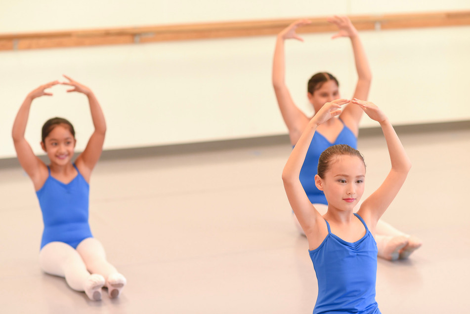 Three young ISB ballet dancers sitting on the floor with their legs stretched out in front of them and their arms in high fifth at the studio in Eastlake, CA.