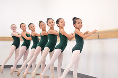 Seven young ISB ballet dancers at the barre doing a tendu derriere at the studio in Chula Vista, CA.