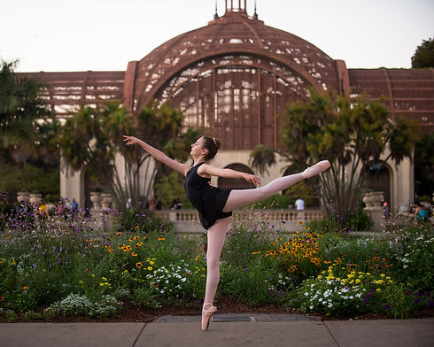 ISB teen ballet dancer posing in a first arabesque position on pointe in front of the Botanical Garden at Balboa Park in San Diego, CA.