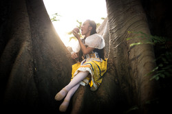 Advanced Inspire School of Ballet dancer dressed in Snow White costume, sitting on a tree, eating a