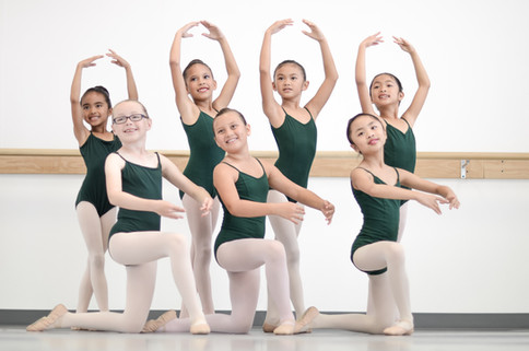 Young ballet dancers at ISB posing for picture at studio in Eastlake, CA. 4 students are standing with their arms in fifth position. Three students are kneeling with their arms in first position.