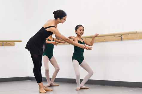 Young ISB ballet students doing a demi plie from first position at the barre, with Ms. Felicia correcting their posture at the studio in Chula Vista, CA.