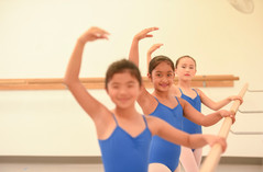 Three young ISB ballet students at the barre with one arm raised to fifth position.