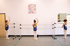 Level 3 ISB dancer posing at the barre with their back facing us. One arm is in high fifth, her feet are in first position.