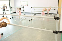 Fairy Tale Ballet ISB dancers working on their port de bras at the barre.