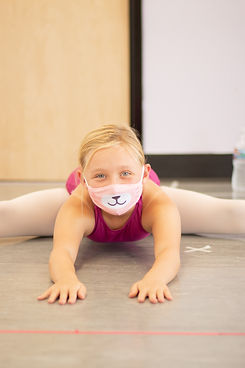 Level 4 ISB ballet student stretching her middle splits on the floor and reaching in front of her. Student is wearing a mask.