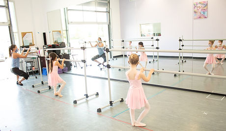 Fairy Tale Ballet ISB dancers learning grand plies from first position while facing the barre and holding on with both hands.
