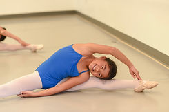 Introductory level ISB ballet dancer posing in the middle splits with one arm arching over to reach her opposite foot at studio in Chula Vista, CA.