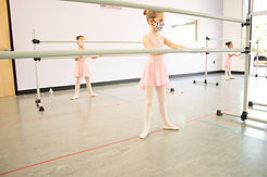 Fairy Tale Ballet dancer holding onto the barre with 2 hands. Students are socially distanced and wearing masks.