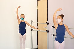 Academy Level 3 ISB ballet dancers standing by the barre at studio in Chula Vista, CA. Dancers are 6 feet apart and wearing face masks.
