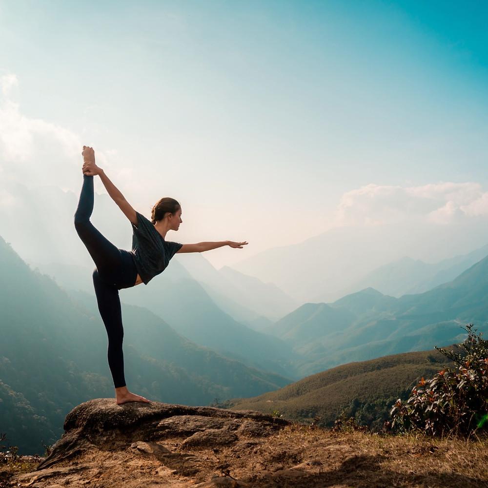 Jeune femme exécutant un mouvement de Yoga sur une montagne en plein jour.