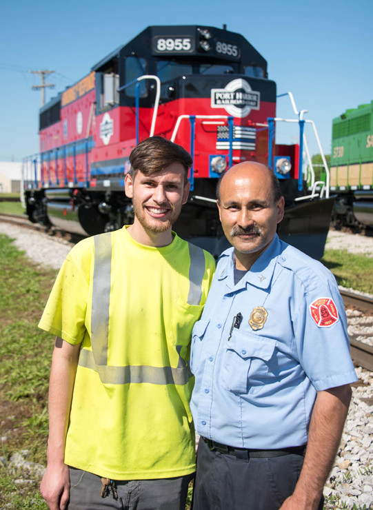 Port Harbor's Dominic Montero, left, designed the paint schemes for the two locomotives. He was joined at the unveiling by his father, Mario, of the St. Louis Fire Department.